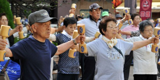 Elderly people work out with wooden dumb-bells in the grounds of a temple in Tokyo on September 17, 2012...