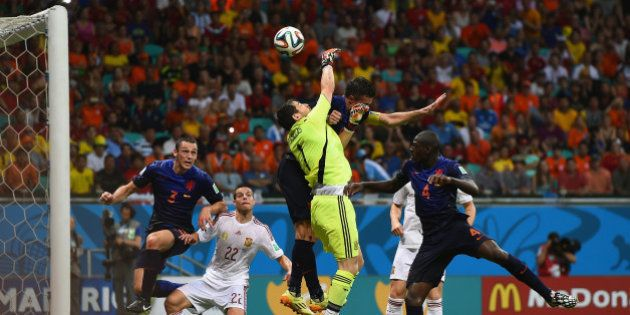 SALVADOR, BRAZIL - JUNE 13: Iker Casillas of Spain and Robin van Persie of the Netherlands collide in...
