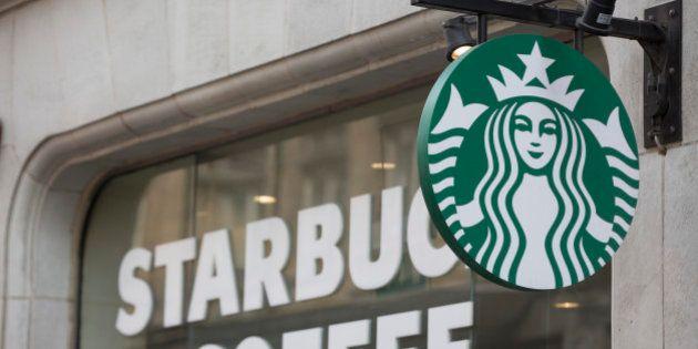 The Starbucks Corp. logo hangs outside of a coffee shop in London, U.K., on Monday, June 9, 2014. U.K....