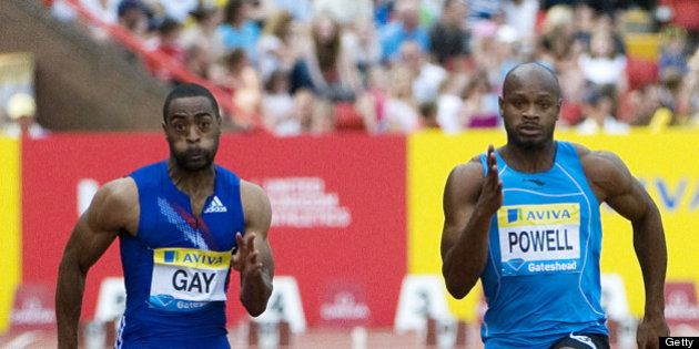 US Tyson Gay (L) runs to win the battle against Jamaica's Asafa Powell (R) in the mens 100m final at...