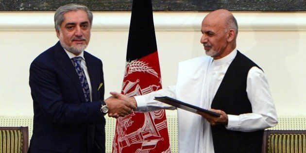 Afghan presidential candidates Abdullah Abdullah (L) and Ashraf Ghani Ahmadzai shake hands after signing...