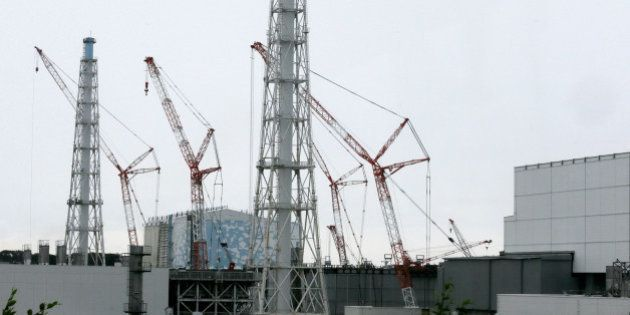 Cranes operate at Unit 3, center, standing next to Unit 4, right, at Tokyo Electric Power Co.'s (Tepco)...