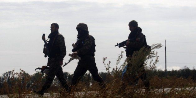 Ukrainian soldiers walk at a checkpoint controlled by Ukrainian forces on September 10, 2014, near the...