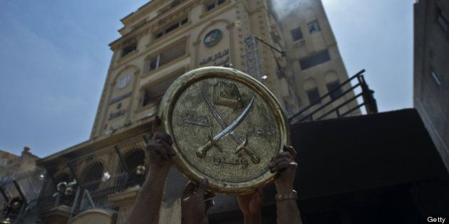 Egyptians hold a plaque of the Muslim Brotherhood emblem which was removed from the party's burnt headquarters...