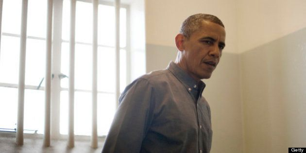 US President Barack Obama visits the cell where Nelson Mandela, an anti-apartheid activist, was once...