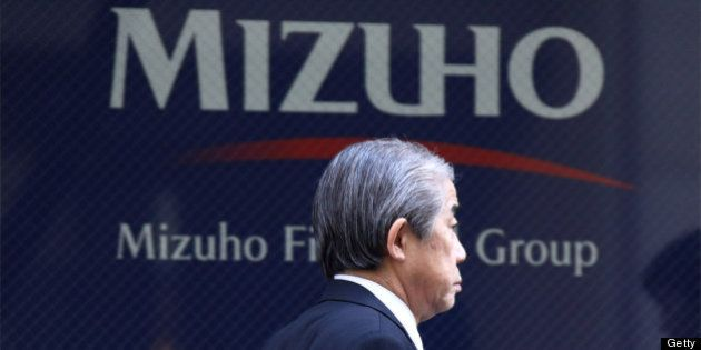 A pedestrian walks past the Mizuho Financial Group Inc. headquarters in Tokyo, Japan, on Tuesday, Feb....