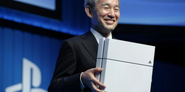 Atsushi Morita, president of Sony Computer Entertainment Japan Asia, holds a PlayStation 4 (PS4) games...