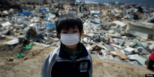 A boy stands among destroyed houses and debris in the tsunami-damaged town of Yamada, in Iwate prefecture,...