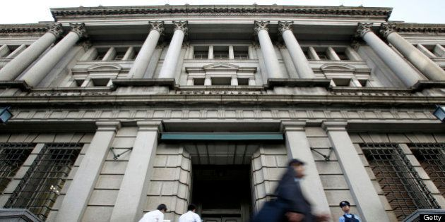 Pedestrians walk past the Bank of Japan headquarters in Tokyo, Japan, on Thursday, October 27, 2011....
