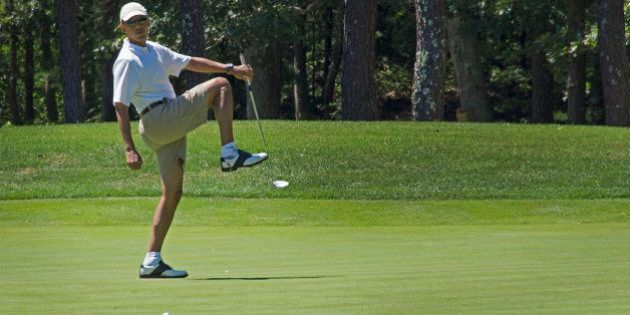 US President Barack Obama reacts to a missed putt on the first green at Farm Neck Golf Club in Oak Bluffs,...