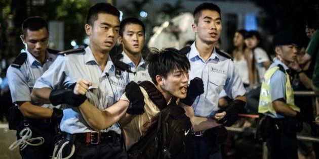 Policemen remove protesters in the central district after a pro-democracy rally seeking greater democracy...
