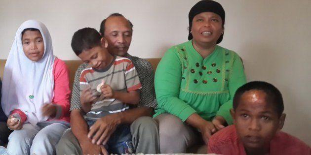 Septi Rangkuti (2nd L) holds his son Jumadi Rangkuti next to his wife Jamaliah (top R) and daugther Raudhatul...