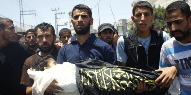 Palestinian mourners carry the body of four-year-old girl Sarah Sheik al-Eid after she was killed along...