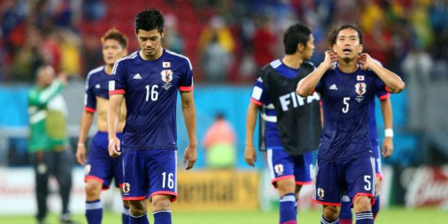 RECIFE, BRAZIL - JUNE 14: Hotaru Yamaguchi (L) and Yuto Nagatomo of Japan walk off the field after losing...