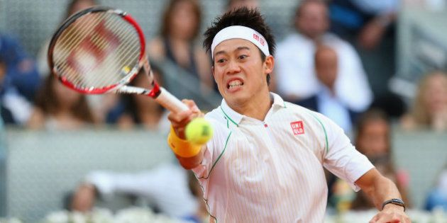 MADRID, SPAIN - MAY 11: Kei Nishikori of Japan plays a forehand against Rafael Nadal of Spain in their...
