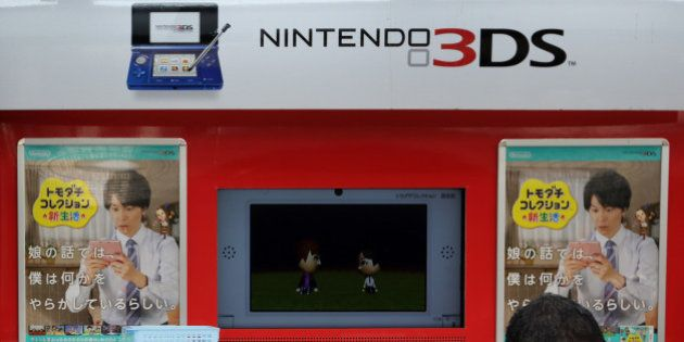 A pedestrian walks past an advertisement for Nintendo Co.'s 3DS handheld game console outside an electronics...