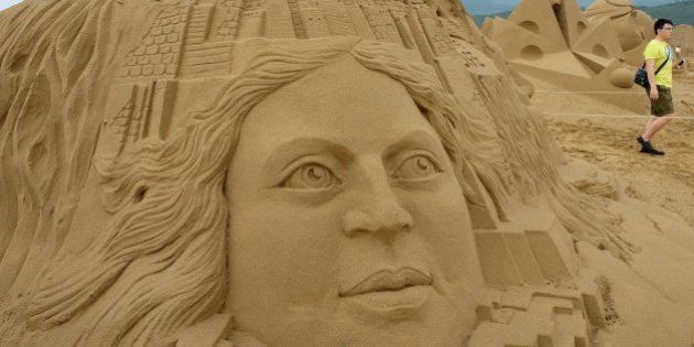 A visitor walks past a sand sculpture named 'The Journey to Me' made by Netherlands artist Lars Borst...