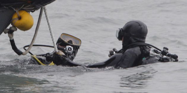JINDO-GUN, SOUTH KOREA - APRIL 19: Divers with the South Korean Navy search for missing passengers at...