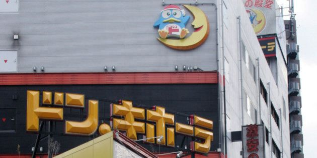 JAPAN - FEBRUARY 23: A shopper leaves a Don Quijote Co. Ltd. discount store in Tokyo, Thursday, February...
