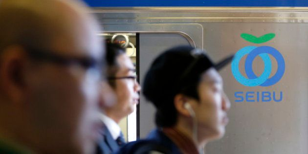 Passengers walk past the Seibu Railway Co. logo displayed on a train at a train station in Tokyo, Japan,...