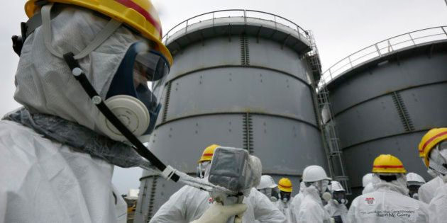 A Tokyo Electric Power Co. (Tepco) employee, left, wearing a protective suit and mask measures radiation...
