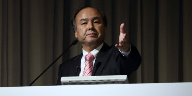 Billionaire Masayoshi Son, chairman and chief executive officer of SoftBank Corp., gestures to a reporter...