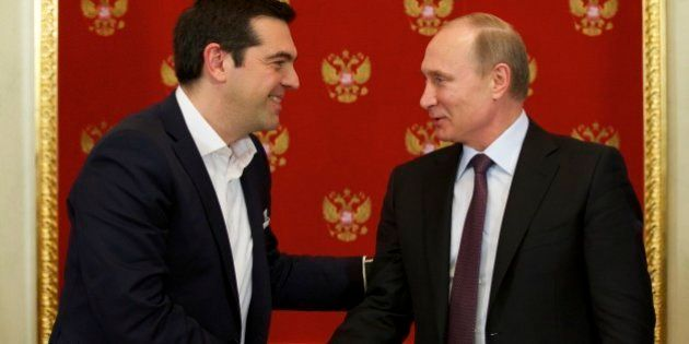 Russian President Vladimir Putin, right, and Greek Prime Minister Alexis Tsipras shake hands during a...