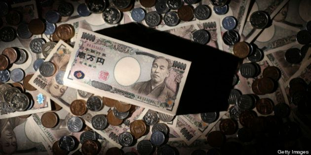 Japanese 10,000 yen banknotes and coins of various denominations are arranged for a photograph in Tokyo,...
