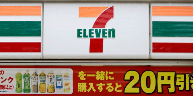 A woman enters a 7-Eleven convenience store, operated by Seven & I Holdings Co., in Kawasaki City, Kanagawa...
