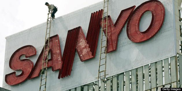 Hanoi, VIET NAM: A worker climbs atop an advertising billboard for Japanese company Sanyo, being installed...