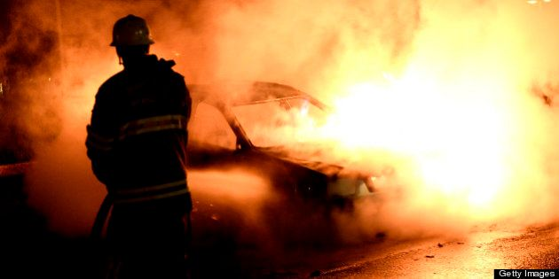 Firemen extinguish a burning car in Kista after youths rioted in few differant suburbs around Stockholm...