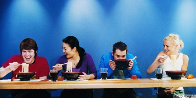 Four Young People Eating Noodles From Bowls at a Table in a Japanese