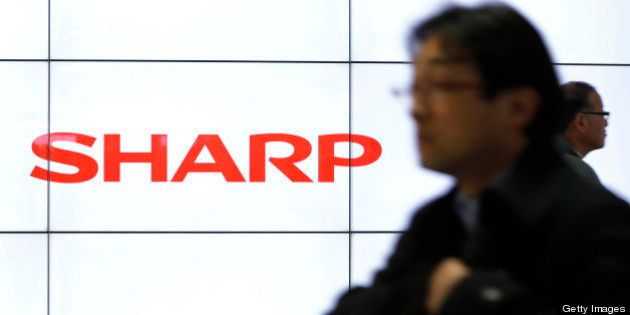 Pedestrians walk past liquid crystal display (LCD) monitors displaying the Sharp Corp. logo at a train...