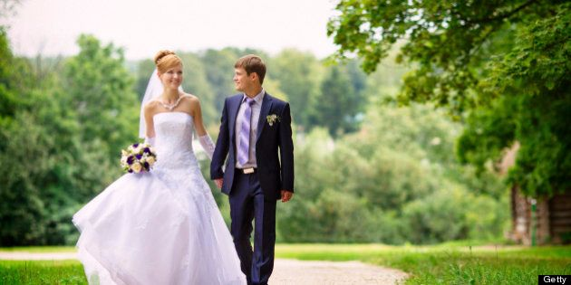 Newly married couple walking down the avenue in the forest
