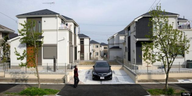 A man walks past residential properties in Yokohama, Kanagawa Prefecture, Japan, on Wednesday, April...