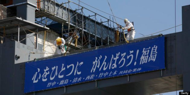 Workers wearing protective suits and masks stand on the construction site of a storage unit for melted...