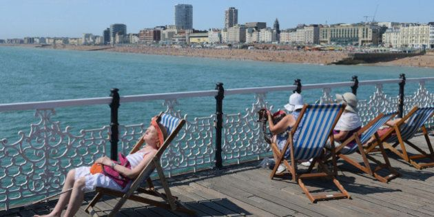 BRIGHTON, ENGLAND - AUGUST 01: People relax in the mini heatwave on the pier at Brighton beach on August...