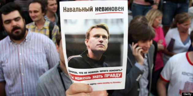 A protester holds a portrait of opposition leader Alexei Navalny, sentenced to five years in a penal...