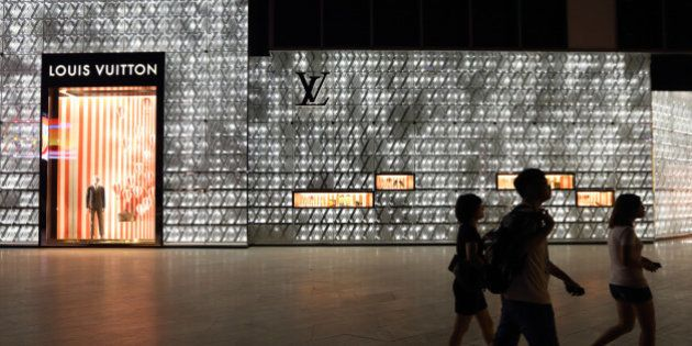 Pedestrians walk past a Louis Vuitton store, operated by LVMH Moet Hennessy Louis Vuitton SA, as it stands...