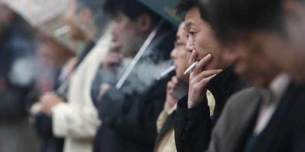 People smoke cigarettes in Tokyo, Japan, on Friday, Dec. 11, 2009. Yoshiyasu Okihira, an analyst at Credit...