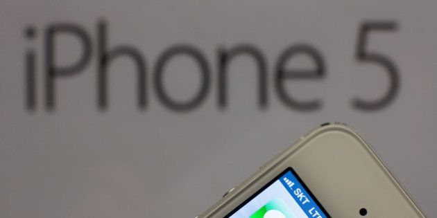 An Apple Inc. iPhone 5 is arranged for a photograph during a launch event organized by SK Telecom Co....