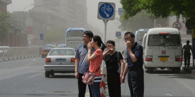 People try to protect themselves against air pollution and dust along a street in Beijing on May 19,...