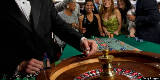 Excited friends gambling at roulette table in