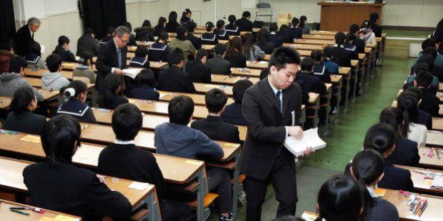 FUKUOKA, JAPAN - FEBRUARY 25: (CHINA OUT, SOUTH KOREA OUT) University staffs distrubute the papers at...