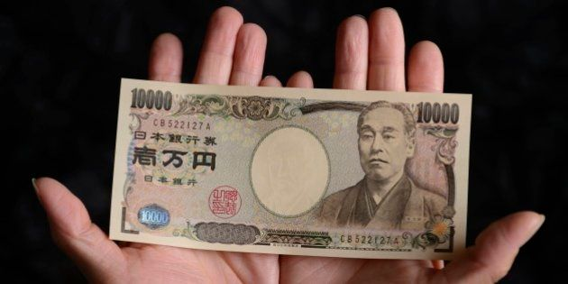 A Japanese 10,000 yen banknote is arranged for a photograph in Kawasaki, Kanagawa Prefecture, Japan,...