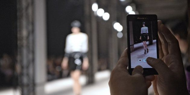 PARIS, FRANCE - SEPTEMBER 25: A model is recorded on smart phones and iPhones as she walks the runway...
