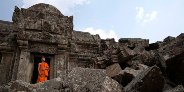 PREAH VIHEAR, CAMBODIA - FEBRUARY 8: A Cambodian monk looks out from inside the 11th century Preah Vihear...