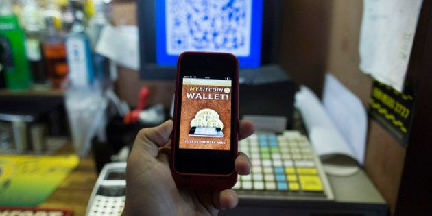 An Apple Inc. iPhone5 displays the Bitcoin smartphone app in this arranged photograph at the bar of the...
