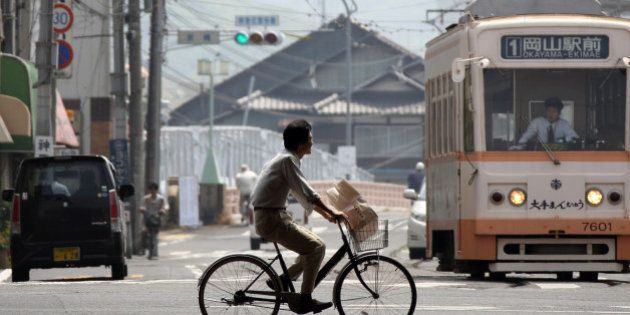 A man rides a bicycle past a tram in Okayama, Japan, on Tuesday, May 21, 2013. The Bank of Japan, forecast...