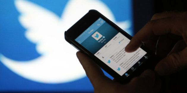 A user scrolls through a Twitter feed on the screen of an Apple Inc. iPhone 5 smartphone in this arranged...